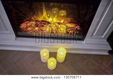 Fireplace with burning woods inside and candles on the floor.