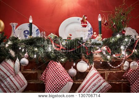 Mantelshelf decorated to christmas holidays with conifer branches, balls, candles, gift boots.