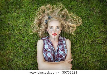 Sensual girl blonde lying on the grass