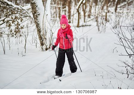 Girl slides on skis through the snowy forest.