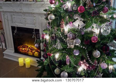 Decorated Christmas firtree and fireplace in room.
