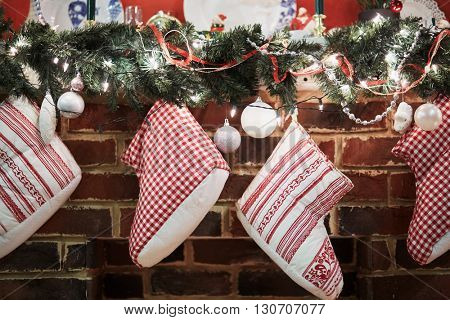Gift boots hang on mantelshelf decorated to christmas holidays with conifer branches, balls, candles.