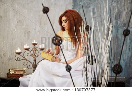 Red-haired woman in white dress sits reading book on old black grand piano lid.