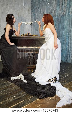 Red-haired woman in white dress and dark-haired woman in black dress stretch necklace with fingers above old grand piano.