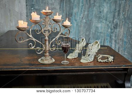 Old black grand piano with burning candles in candlestick, glass of red wine, high-heeled shoes and necklace on lid in room with ragged walls.