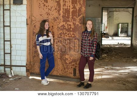 Two teen girls standing at the old iron door in an abandoned building.