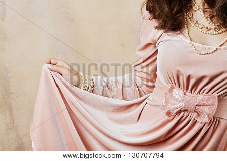 Young woman holds by hand hem of her pink dress standing at wall in studio.