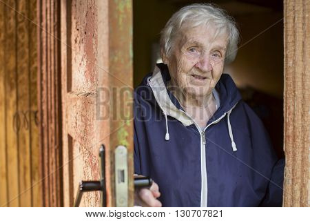 An old woman peeks out from behind the door of his house.