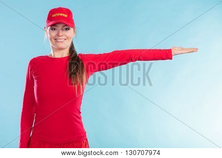 Happy Lifeguard Woman In Cap Pointing Direction.