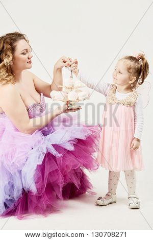 Mother and little daughter hold two-story dish with marshmallows.
