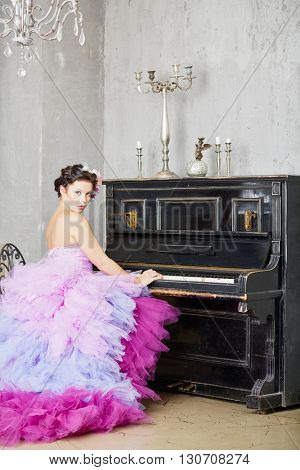 Woman in fluffy purple dress sits on piano-stool at old piano in room with ragged walls.