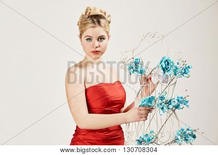 Half-length portrait of woman in a red dress puts artificial flowers into the metal female mannequin.
