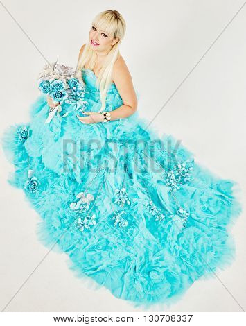 Smiling woman in blue fluffy dress with bunch of artificial flowers, view from above.