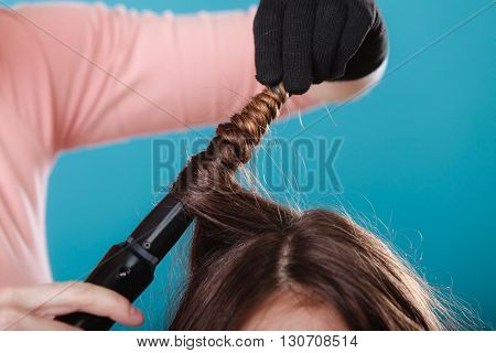 Hairdresser curling woman hair with electric iron curler tong. Hairstylist making girl hairstyle. Beauty.