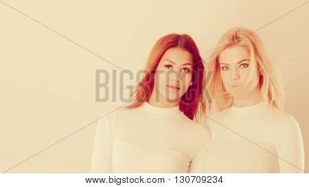 Friends people concept. Two young friends together. Girls have white top standing next to each other. One lady has blonde hair second dark ones.