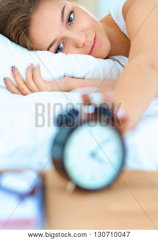 A young woman putting her alarm clock off in the morning.