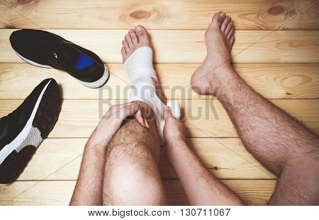 Man leg bandage sitting on the wooden floor. Sports injuries. top view