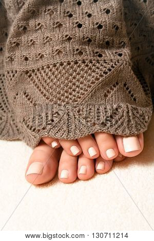 Legs with a beautiful beige manicure in the warm, cozy blanket brown lace