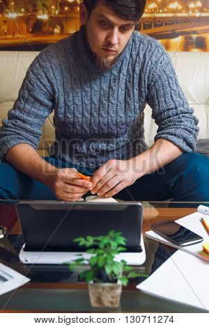 A man sitting at a desk, writing a pencil in a notebook . Telework concept