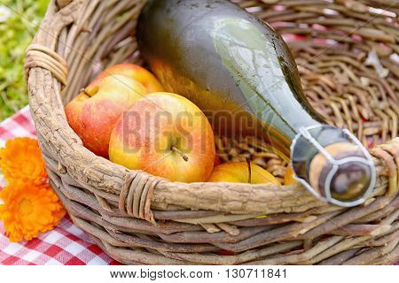 a bottle of cider with apples in a basket