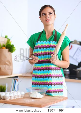 Woman is making cakes in the kitchen .