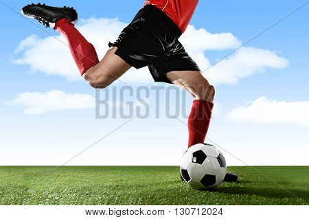 close up legs of football player in red socks and black shoes running and kicking the ball in free kick action playing outdoors on green grass pitch under a blue sky