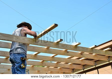 Man building roof add on too shop.  Active middle age senior working on DYI construction project