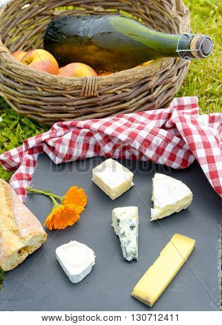 some apples with cider and french cheese in the grass