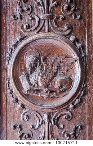 Winged lion engraved on the wooden portal of a medieval church.