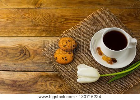 Cup of tea and white tulip on sackcloth top view copy space. Cup of tea. Tea cup. Homemade cookies. Sweet pastry. Breakfast tea