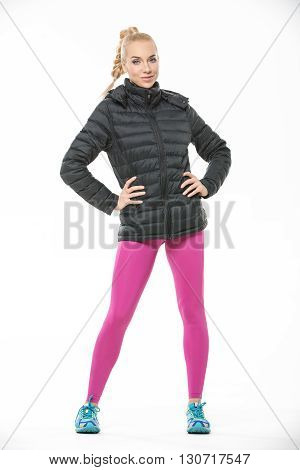 Young blonde girl in the sportswear stands on the white background in the studio. She wears cyan-yellow sneakers, pink pants and black jacket. She holds her hands on her waist. She looks into the camera with a smile. Vertical.