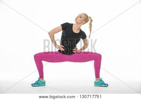 Young blonde gymnast in the sportswear squats with divorced feet on the white background in the studio. She wears cyan-yellow sneakers, pink pants and black t-shirt. She holds her hands on the waist. She has a plait on her head. She looks right and up. Ho