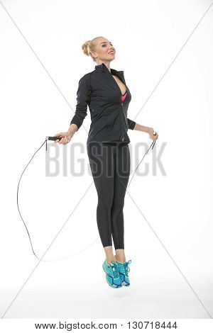 Pretty blonde girl in the sportswear jumps with skipping rope on the white background in the studio. She wears cyan-yellow sneakers, black pants, pink-black t-shirt and black hoody. Her feet are off the floor. She looks up with a smile. Vertical.
