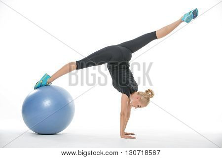 Attractive blonde girl in the sportswear with a blue fitball on the white background in the studio. She wears cyan-yellow sneakers, black pants and black t-shirt. She leans on her hands while her right leg is on the fitball and left leg is elongated to th