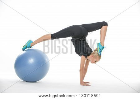 Blonde gymnast girl in the sportswear with a blue fitball on the white background in the studio. She wears cyan-yellow sneakers, black pants and black t-shirt. She leans on her hands while her right leg is on the fitball and left leg is near her head. Pho