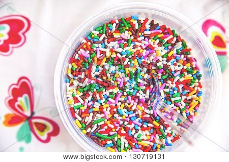 a bowl full of colorful candy sprinkles with a clear plastic spoon in them and a plastic tablecloth