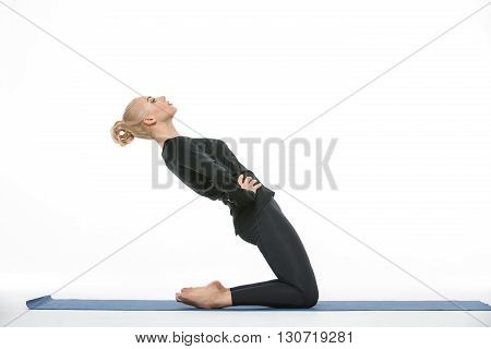 Young blonde girl in the sportswear stands on the knees on a blue gymnastic mat on the white background in the studio. She wears black pants and black long sleeve t-shirt. She is barefoot. Her hands are on the waist. She tilts her body back. She looks for