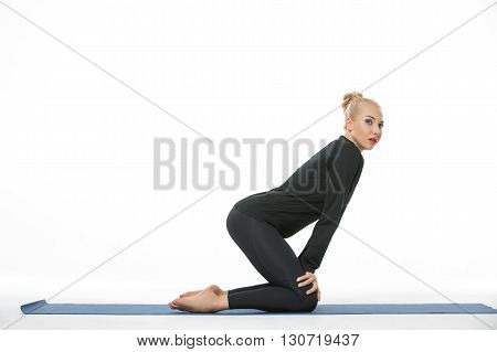 Sexy blonde girl in the sportswear stands on the knees on a blue gymnastic mat on the white background in the studio. She wears black pants and black long sleeve t-shirt. She is barefoot. Her hands are on the knees. She tilts her body forward. She looks t