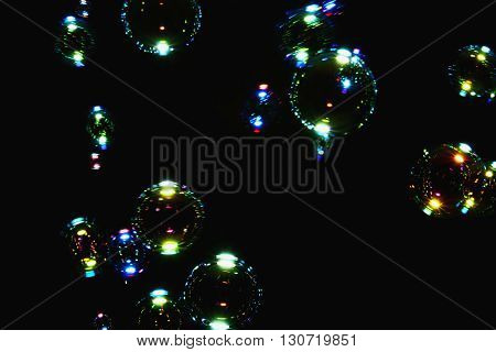 Blurred colorful air bubbles from the soap bubbles on black background.