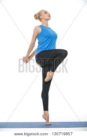 Attractive blonde girl in the sportswear stands partially sideways on the left leg on a blue gymnastic mat on the white background in the studio. She wears black pants and blue sleeveless t-shirt. She is barefoot. She holds her stretched hands together be