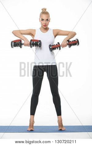 Sexy blonde girl in the sportswear with dumbbells in her hands stands on a blue gymnastic mat on the white background in the studio. She wears black pants and white sleeveless t-shirt. She is barefoot. Her hands are raised. She looks into the camera. Vert