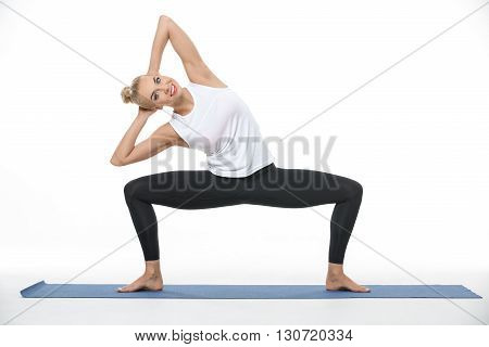 Smiling blonde girl in the sportswear squats with divorced feet on a blue gymnastic mat on the white background in the studio. She wears black pants and white sleeveless t-shirt. She is barefoot. She holds her hands on the nape and tilts torso to the righ