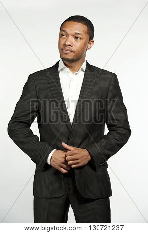 A young chic black male model wearing a white button down shirt with a custom suit jacket in a studio setting on a white background.