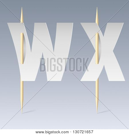 White paper cut font on toothpicks on grey background. W and X letters