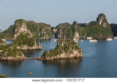 Distant View of the lush green covered limestone karsts formation on Ha Long Bay in Vietnam. The clear blue sky looks gorgeous. Tourist boats are seen sailing on the blue water.