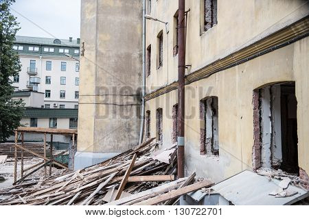 Part of an old building in Minsk city being reconstructed again. Broken wooden furnitures lay in front of the building as it is rebuilt and renovated.