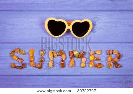 Inscription summer made of amber stones and sunglasses on purple boards summer and vacation time