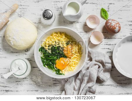 Raw ingredients for baking a pie with spinach - eggs cheese dough spinach cream on light wooden background. Baking rustic background