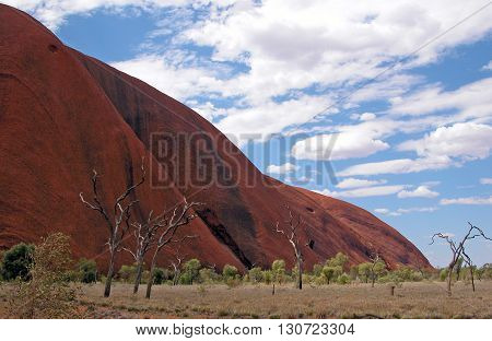 Iconic Uluru in the red centre of Australia with a cloud filled blue sky above