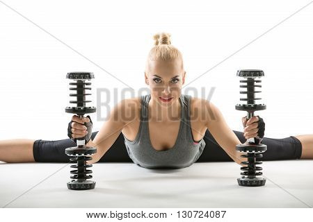 Blonde girl in the sportswear makes the splits on the white background in the studio. She wears black pants, gray sleeveless t-shirt and dark sports gloves. She holds the dumbbells while her torso tilted forward. She looks into the camera with a smile. Ho